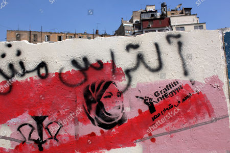 "Graffiti depicting female activist Samira Ibrahim, who was forced to undergo a virginity test while in detention by the military, and Arabic that reads, ""Ultras, paint the streets of Egypt,"" is seen in downtown Cairo, Egypt. After Egypt's ruling military sealed off streets around Cairo's Tahrir Square with walls of imposing concrete blocks, a group of artists decided to reopen the avenues on their own in the public imagination, at least"
