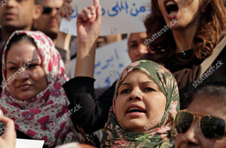 "Samira Ibrahim Activist Samira Ibrahim, center, chants slogans at a demonstration against a court ruling that cleared a military doctor of charges he forced a ""virginity test"" on female activists, in front of the high court in Cairo, Egypt, . Protesters on Friday carried posters of Samira Ibrahim, the young female activist who filed a lawsuit against a military doctor accusing him of subjecting her to a ""virginity test"" last year after she was detained by the army during a protest"