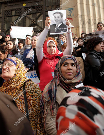 "An Egyptian woman holds up a satirical poster at a demonstration against a court ruling that cleared a military doctor of charges he forced a ""virginity test"" on female activists, in front of the high court in Cairo, Egypt, . Protesters on Friday carried posters of Samira Ibrahim, the young female activist who filed a lawsuit against a military doctor accusing him of subjecting her to a ""virginity test"" last year after she was detained by the army during a protest. The writing on the placard reads, in Arabic, ""the president of Abbassiya"