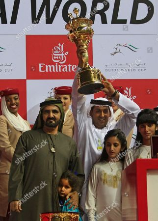 A photo from files showing Sheikh Mohammed bin Rashid Al Maktoum, prime minister and ruler of Dubai, on his left, Mahmoud Al Zarooni, the trainer of Monterosso from Great Britain holds the trophy after they won the Dubai World Cup race in Dubai, United Arab Emirates. The doping scandal that led to the downfall of Godolphin trainer Mahmood al-Zarooni is now helping fuel a call for an outright ban on anabolic steroids in horse racing