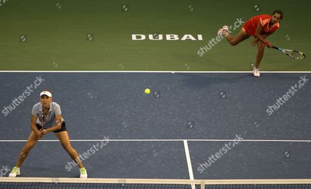 Sania Mirza from India, right, serves the ball as Elena Vesnina from Russia looks on during their doubles final against South Africa's Liezel Huber, right, and Lisa Raymond of the United States at Dubai Duty Free Tennis Championships, in Dubai, United Arab Emirates