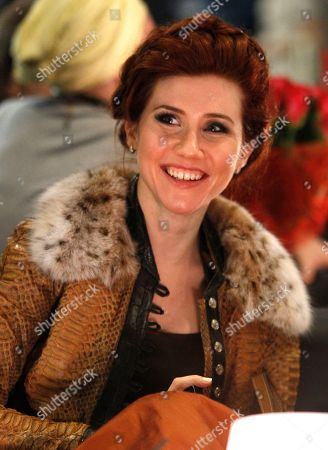 Russian Anna Chapman, who was deported from the U.S. in July 2010 on charges of espionage, watches models display creations by Turkish designer Cengiz Abazoglu during Fashion Week in Moscow, Russia