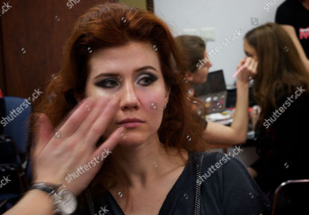 Anna Chapman A stylist makes-up Anna Chapman, who was deported from the U.S. on charges of espionage, at a backstage preparing to display a creations by I Love Fashion, France, during Fall-Winter 2012 - 2013 collection at Mercedes-Benz Fashion Week in Moscow, Russia