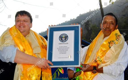 Apa Sherpa Craig Glenday, the editor-in-chief of the Guinness World Records, left, hands a certificate to veteran climber Apa Sherpa for the most number of successful ascents of Mount Everest, at Sindupalchok district, about 80 kilometers (50 miles) north of Katmandu, Nepal. Guinness officials have felicitated Sherpa for his world record of climbing Mt. Everest 21 times