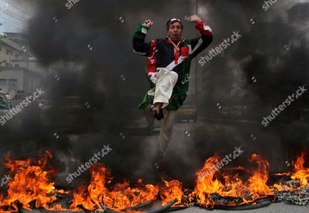 A supporter of ruling People's party jumps over tires burn by protester to condemn Pakistan's judiciary in Peshawar, Pakistan on . Pakistan prime minister Yousuf Raza Gillani has challenged the opposition to unseat him in a fiery speech a day after he was convicted by the Supreme Court for contempt
