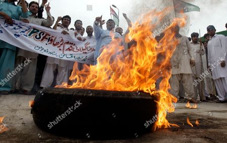 "Supporters of ruling People's party burn a tyres during a protest against supporters of opposition party Pakistan Muslim League in Peshawar, Pakistan, on . Pakistan Prime Minister Yousuf Raza Gillani has challenged the opposition to unseat him in a fiery speech a day after he was convicted by the Supreme Court for contempt. Banner reads "" go ahead Yousuf Raza Gilani, we are with you"