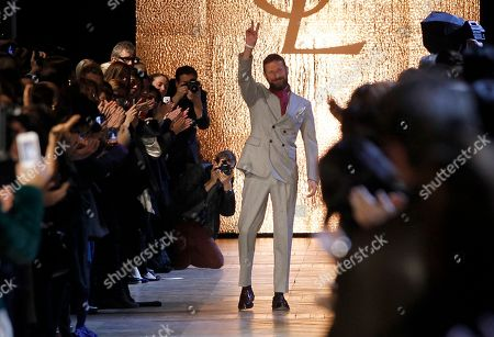 Italian designer Stefano Pilati waves after the presentation of his collection for Yves saint Laurent as part of the Fall-Winter, ready-to-wear 2013 fashion collection, during Paris Fashion week