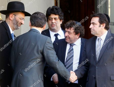Nicolas Sarkozy, Joel Mergui, Gilles Bernheim France's President Nicolas Sarkozy, second left back turned, shakes hands with France's Jewish central Consistory President Joel Mergui, right, as Grand Rabbi of France Gilles Bernheim, left, looks, after a meeting with representatives of French Jewish and Muslim communities at the Elysee Palace in Paris, . Sarkozy met the representatives the day after a gunman on a motorbike opened fire Monday at a Jewish school in the French city of Toulouse, southwestern France, killing a rabbi and his two young sons as they waited for a bus, then chased down a 7-year-old girl, shooting her dead at point-blank range. The latest in a series of attacks on minorities that have raised fears of a racist killer on the loose