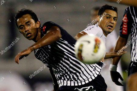 Brazil's Vasco da Gama's Eder De Oliveira and Peru's Alianza Lima's Joahzino Arroyo, left, eye the ball during a Copa Libertadores soccer match in Lima, Peru