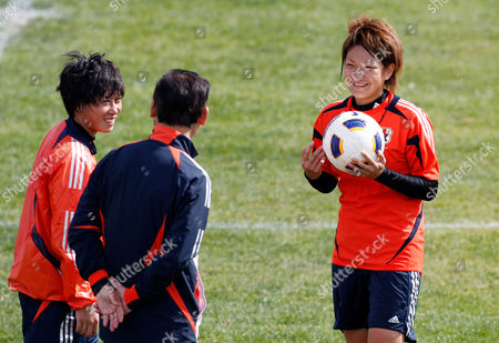 Players Megumi Takase, left, and Yuika Sugasawa smile while listening to head coach Norio Sasaki, center, during a training session of Japan's women's soccer team, in Quarteira, southern Portugal. On Wednesday Japan will play Germany in the final of the Algarve Cup
