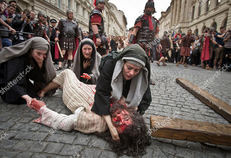 """Romanian Jewish actress Maia Morgenstern, center, daughter of Holocaust survivors, best known for playing Mary in Mel Gibson's passion-stirring Biblical epic 'The Passion of the Christ"""" holds Dan Les during a reenactment of the crucifixion of Jesus Christ in Bucharest, Romania, . Romania's orthodox majority will celebrate Easter on Sunday April 15"""