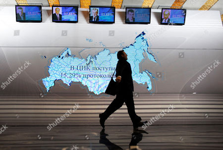 A man walks past a map of Russia and portraits of presidential candidates, from left: Vladimir Zhirinovsky, Gennady Zyuganov, Sergei Mironov, Mikhail Prokhorov and Vladimir Putin at the Putin's headquarters in Moscow, Russia, . Prime Minister Vladimir Putin won Russia's presidential election on Sunday, according to exit polls cited by state television, but the vote was tainted by widespread violations claimed by the opposition and independent observers