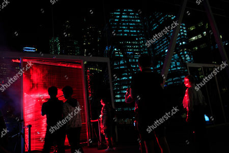 Viewers are silhouetted against a laser light frame art installation created by China's artist Li Hui displayed as part of the iLight Marina art exhibition along the waterfront of Singapore's Marina Bay while the financial district is seen in a reflection in Singapore