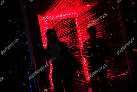 Viewers are silhouetted against a laser light frame art installation created by China's artist Li Hui displayed as part of the iLight Marina along the waterfront of Singapore's Marina Bay in Singapore