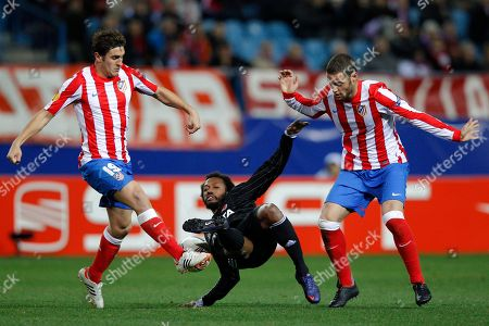 Stock Picture of Manuel Fernandes, Jorge Resurreccion Merodio 'Koke', Mario Suarez Atletico de Madrid's Jorge Resurreccion Merodio 'Koke', left, and Mario Suarez, right, duels for the ball with Besikta's Manuel Fernandes from Portugal, center, during a Europa League first leg round of 16 soccer match, at the Vicente Calderon stadium, in Madrid