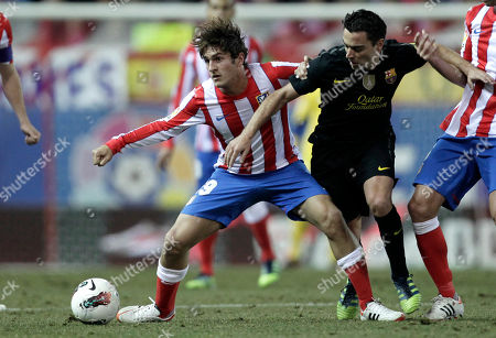 Atletico de Madrid's Jorge Resurreccion Merodio 'Koke', left, controls the ball against FC Barcelona's Xavi Hernandez during a Spanish La Liga soccer match at the Vicente Calderon Stadium in Madrid