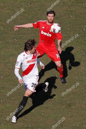 Miguel Perez Cuesta, Xabi Alonso Real Madrid's Xabi Alonso, right, duels for the ball with Rayo Vallecano's Miguel Perez Cuesta during their Spanish La Liga soccer match, at the Vallecas stadium, in Madrid