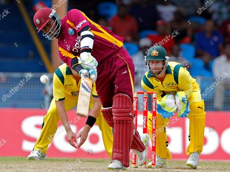 Stock Photo of West Indies' Marlon Samuels hits a six off Australia's Xavier Doherty, unseen, as the wicket keeper Matthew Wade looks on during their first one day international cricket match in Kingstown, St. Vincent