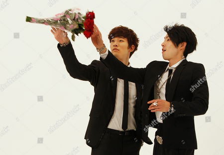 "Junho, Vanness Wu Junho from Korean boy band 2PM, left, and Vanness Wu, formerly of Taiwan's boy band F4, reach for a tossed bouquet of roses as they rehearse scenes from a new music video collaboration for the song ""Unbeatable"" together in Taipei, Taiwan"