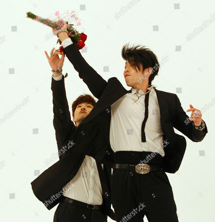 "Junho, Vanness Wu Junho from Korean boy band 2PM, left, and Vanness Wu, formerly of Taiwan boy band F4, reach for a tossed bouquet of roses as they rehearse scenes from a new music video collaboration for the song ""Unbeatable"" together in Taipei, Taiwan"
