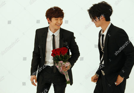 "Junho, Vanness Wu Junho from Korean boy band 2PM, left, holding a tossed bouquet of roses laughs with Vanness Wu formerly of Taiwanese boy band F4, as they rehearse scenes from a new music video collaboration for the song ""Unbeatable"" together in Taipei, Taiwan"