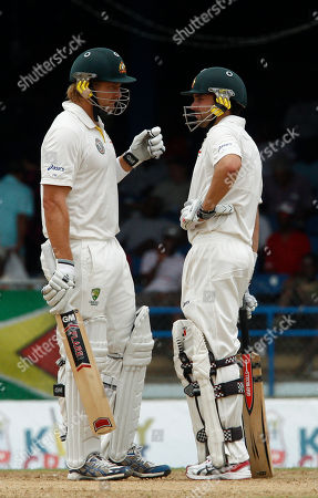 Australia's Shane Watson, left, talks with his partner batsmen Ed Cowan during the opening day of their second cricket Test match in Port of Spain, Trinidad