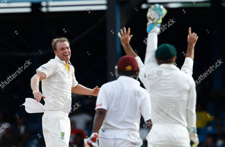 Australia's bowler Michael Beer, left, celebrates after the umpire ruled the LBW of West Indies' batsman Kraigg Brathwaite, center, to dismiss during the second day of their second cricket Test match in Port of Spain, Trinidad