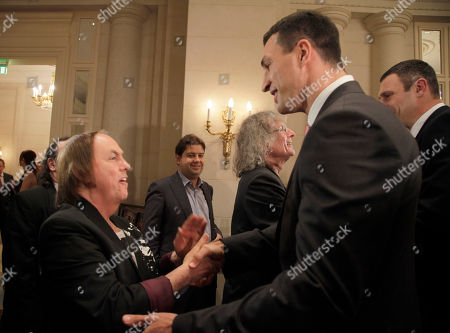Wladimir Klitschko, Dave Hill, Don Powell Heavyweight World Boxing Champion Wladimir Klitschko, second right, shakes hands with guitarist of British legendary rock group Slade Dave Hill, left, while Wladimir's brother Vitali, first right background, greets Slide's drummer Don Powell during the Charity Gala Dinner of Klitschko Brothers Foundation in Kiev, Ukraine, . Hill and Powell donated a guitar with their autographs for the charity auction. Funds raised from the auction were planned for children sports and education in Ukraine