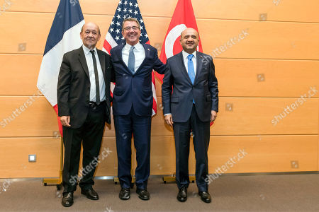 Stock Photo of France's Defense Minister Jean-Yves Le Brian, left, Turkey's Defense Minister Fikri Isik, right, and U.S Secretary of Defense Ash Carter pose for the media prior to a meeting of the North Atlantic Council in Defense Ministers session at NATO headquarters in Brussels on . NATO defense ministers met in Brussels to discuss tense relations with Russia, how to help Middle East nations combat extremism and cooperation between the military alliance and the European Union