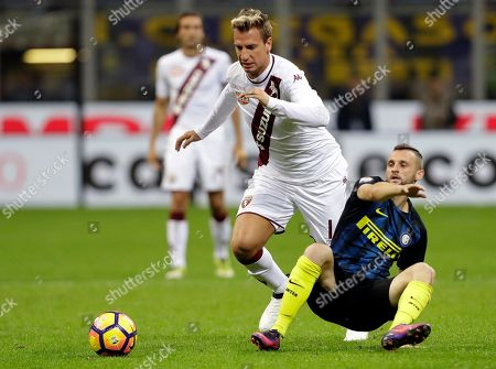 Torino's Maxi Lopez, left, is challenged by Inter Milan's Marcelo Brozovic during aSerie A soccer match at the Milan San Siro stadium