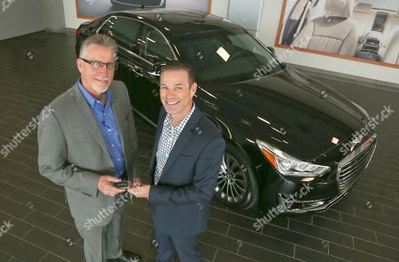 Stock Photo of Russ Johnson, Mike Williams Russ Johnson, right, the first US buyer of the new 2017 Genesis G90, receives the key from Round Rock Genesis general manager Mike Williams at the dealership in Round Rock, Texas on