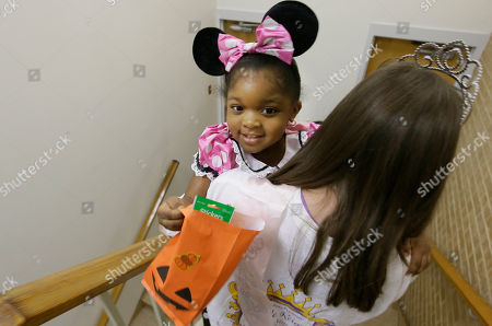 Lindsey Thornton Presley Smith, 3, is carried down stairs as by Lindsey Thornton as they practice trick-or-treating at The University of Texas at Dallas' Callier Center for Communication Disorders preschool class in Dallas, . Smith is part of a classroom-based speech, language and communication program for children with Autism Spectrum Disorder. In the week leading up to Halloween, the children are practicing trick-or-treating. The class they are participating in helps them become better communicators while working to prevent behaviors that could interfere with learning and relationships