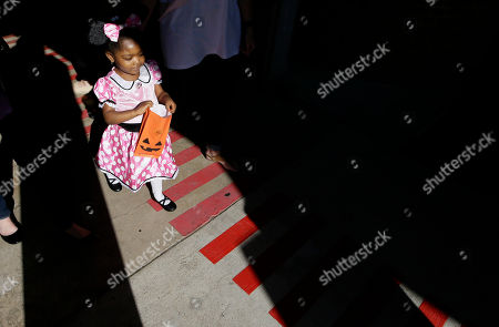 Presley Smith, 3, carries a bag as she practices trick-or-treating at The University of Texas at Dallas' Callier Center for Communication Disorders preschool class in Dallas, . Smith is part of a classroom-based speech, language and communication program for children with Autism Spectrum Disorder. In the week leading up to Halloween, the children are practicing trick-or-treating. The class they are participating in helps them become better communicators while working to prevent behaviors that could interfere with learning and relationships