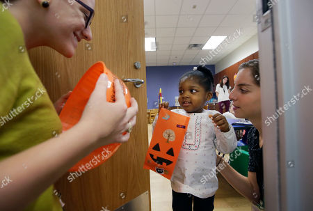 Leah Sack, Kaitlyn Hazlewood In this photo made, Presley Smith, 3, center, practices trick-or-treating with the help of Leah Sack, right, and Kaitlyn Hazlewood at The University of Texas at Dallas' Callier Center for Communication Disorders preschool class in Dallas. Smith is part of a classroom-based speech, language and communication program for children with Autism Spectrum Disorder. In the week leading up to Halloween, the children are practicing trick-or-treating