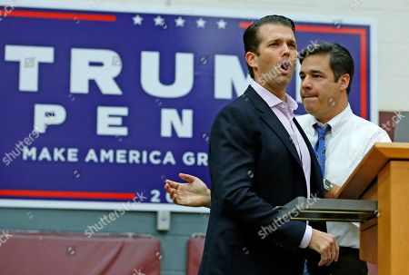 After being introduced by Rep. Raul Labrador, right, R-Idaho, Donald Trump Jr., left, acknowledges the cheering supporters prior to speaking at a campaign rally for his father, Republican presidential candidate Donald Trump, at Arizona State University, in Tempe, Ariz