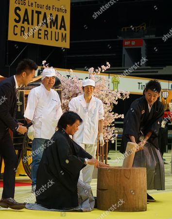 Stock Photo of Japanese cyclists Yukiya Arishiro and Fumiyuki Beppu demonstrate rice-cake pounding in traditional Japanese costume at a special cultural event