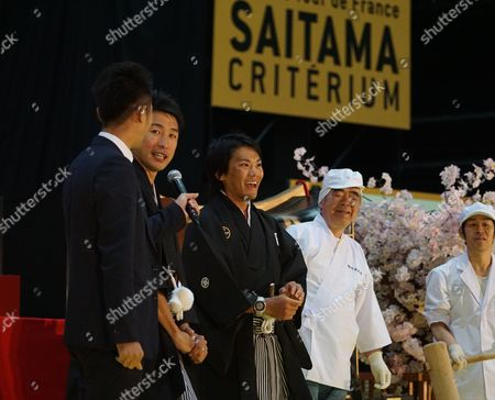 Stock Picture of Japanese cyclists Yukiya Arishiro and Fumiyuki Beppu demonstrate rice-cake pounding in traditional Japanese costume at a special cultural event