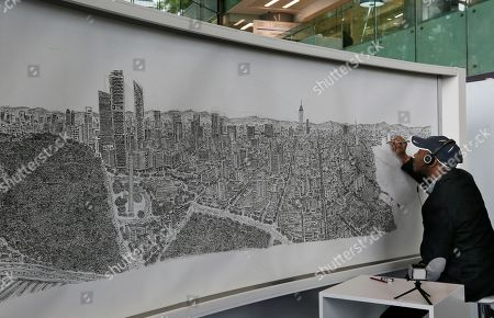 Stock Picture of British artist Stephen Wiltshire draws Mexico City from memory, in the lobby of the BBVA Bancomer Tower on Paseo de la Reforma, in Mexico City . The autistic artist is spending five days creating a panoramic drawing of the megalopolis from memory after taking a sole helicopter flight over the city. Since 2005, the artist has drawn similar large-scale cityscapes of cities including Tokyo, Rome, Dubai, Shanghai, and New York