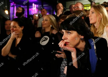 Birgitta Jonsdottir of the Pirate party (Pirater), right, looks at a TV screen in Reykjavik, Iceland, . Parliamentary elections were held in Iceland on Saturday, with more than 250,000 voters entitled to elect 63 members of the Althing parliament
