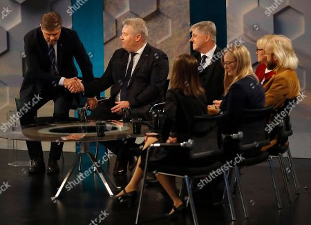 Bjarni Benediktsson of The Independence Party, left, shakes hands with Iceland's Prime Minister Sigurdur Ingi Johannsson in a TV studio in Reykjavik, Iceland, . Parliamentary elections were held in Iceland on Saturday, with more than 250,000 voters entitled to elect 63 members of the Althing parliament