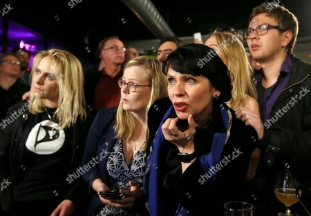 Stock Image of Birgitta Jonsdottir of the Pirate party (Pirater), right, looks at a TV screen in Reykjavik, Iceland, . Parliamentary elections were held in Iceland on Saturday, with more than 250,000 voters entitled to elect 63 members of the Althing parliament