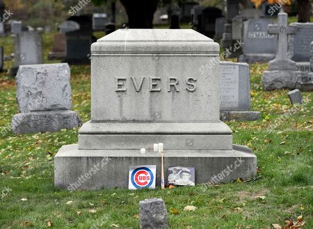 A Chicago Cubs sign is among the items left at the grave of Johnny Evers at St. Mary's Cemetery, in Troy, N.Y. Some Cubs fans are hoping they can break a 108-year-old World Series championship drought by leaving items at the New York grave of the middle man in the team's famed Tinker-to-Evers-to-Chance double-play combination. Evers was the second baseman for the Cubs team that won the 1908 World Series. He was immortalized a few years later in a New York newspaper reporter's 50-word poem, along with future fellow Hall of Famers shortstop Joe Tinker and first baseman Frank Chance