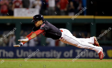Cleveland Indians' Coco Crisp dives into second after a double against the Chicago Cubs during the third inning of Game 7 of the Major League Baseball World Series, in Cleveland