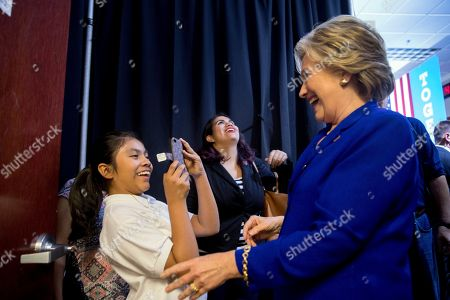 Stock Image of Hillary Clinton, Karla Ortiz Democratic presidential candidate Hillary Clinton, right, laughs as Karla Ortiz, left, takes a photograph of her backstage following a rally at the Plumbers and Pipe fitters Local 525 Union Hall in Las Vegas, . Karla met Hillary Clinton in Nevada and was featured in the campaign ad, Brave