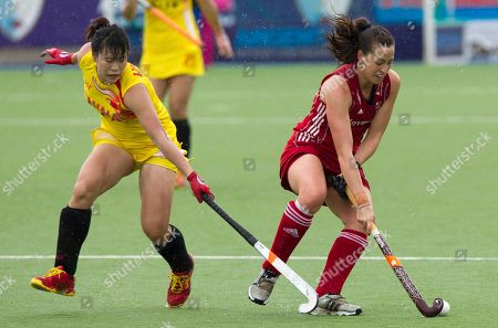 China's Sinan Sun, left, battles for the ball with Emily Maguire of England during their Women's Champions Trophy field hockey match in Rosario, Argentina