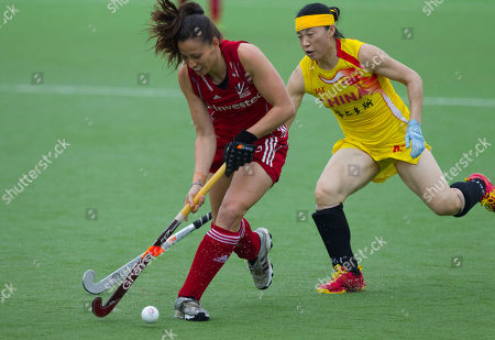 Emily Maguire, left, of England, battles for the ball with China's Chunling Tang during their Women's Champions Trophy field hockey match in Rosario, Argentina