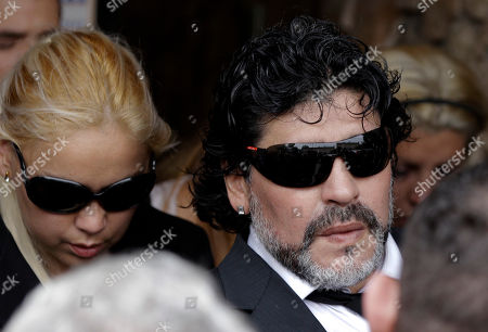 """Argentina's soccer legend Diego Maradona, right, leaves a funeral home after attending the funeral of his mother, Dalma Franco de Maradona, in Buenos Aires, Argentina, . Maradona's mother, widely known as """"Dona Tota,"""" died on Saturday of heart failure. She was 81. The Argentine football great arrived from Dubai, where he coaches Al Wasl in the domestic league. He was told of his mother's failing health and attempted to return home to be at her bedside but was informed of her death during the long flight. Pictured behind Maradona is his girlfirend Veronica Ojeda"""