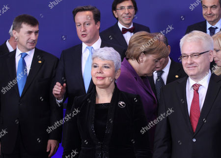 Front row left to right, Croatian Prime Minister Jadranka Kosor and Croatian President Ivo Josipovic. Second row, left to right, Estonia's Prime Minister Andrus Ansip, British Prime Minister David Cameron, German Chancellor Angela Merkel, and Slovakian Prime Minister Iveta Radicova. Back row left to right, Belgium's Prime Minister Elio Di Rupo and Spain's Prime Minister Jose Luis Rodriguez Zapatero during a group photo at an EU summit in Brussels on . The president of the European Council said Friday that a new intergovernmental treaty meant to save the euro currency will include the 17 eurozone states plus as many as six other European Union countries, but not all 27 EU members