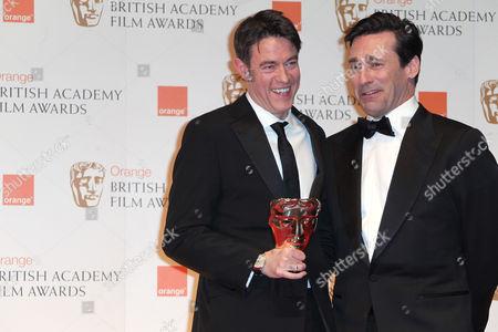 Writer Peter Straughan, left, posing with award for 'Best Adapted Screenplay, for the Film Tinker, Tailor, Soldier, Spy presented by actor Jon Hamm, right,backstage at the BAFTA Film Awards 2012, at The Royal Opera House in London