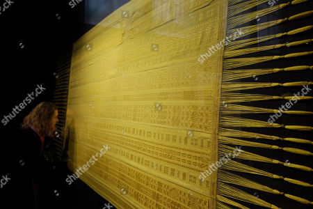 Stock Picture of A visitor looks at a spider silk shawl, designed by Simon Peers and Nicholas Godley, on display at the Victoria and Albert Museum in London, . The shawl is woven and embroidered in Madagascar and is made from the silk of more than a million female Golden Orb Weaver spiders collected in the highlands of Madagascar. The hand-woven textile is naturally golden in colour and took over four years to create